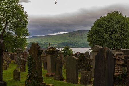 Tombstones in cemetery with flying bird and lake in background, in Luss parish church yard in Scotland