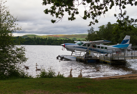 hydroplane: Scenic view of hydroplane and ducks at lake shore in Loch Lomond, Scotland at Cameron Bay