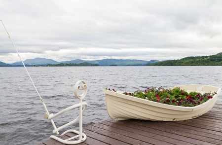 loch lomond: Boat as flower pot and iron fisherman on pier on shores of lake Loch Lomond at Duck Bay in Scotland Stock Photo