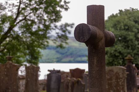 loch: Cross and tombstones in cemetery with lake in background, in Luss parish church yard in Scotland