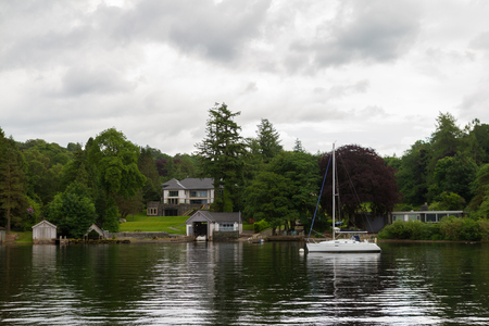 holiday house: Scenic view of boat and houses on Lake Windermere lake-shore on a cloudy day