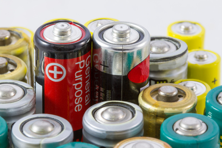AA alkaline batteries with selective focus on two red black protruding batteries Stock Photo
