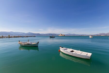 Moored Traditional Fishing Boats, Lightouse and Bourtzi Fortress in the background in Nafplion, Greece- wide-angle Stock Photo