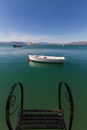 nafplio: Pier Steps, Traditional Fishing Boats and Bourtzi Fortress in the distant background in Nafplion, Greece- portrait photo Stock Photo