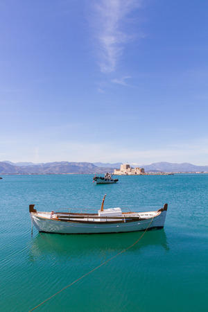 Traditional Fishing Boats and Bourtzi Fortress in the background in Nafplion, Greece- portrait photo