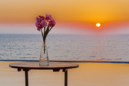 Vase of flowers on table by the swimming pool overlooking sea at sunset in Pomos village, Paphos area, Cyprus Stock Photo