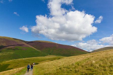 Keswick, United Kingdom - 13 August, 2017: People hiking in Latrigg hill across mount Skddaw overlooking Keswick and lake Derwent Water, Cumbria, UK Editorial