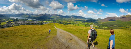 Keswick, United Kingdom - 13 August, 2017: People hiking in Latrigg hill overlooking Keswick and lake Derwent Water, Cumbria, UK