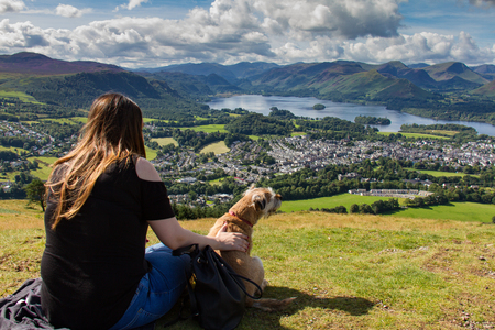 Keswick, United Kingdom - 13 August, 2017: Girl touching dog and gazing at Keswick and lake Derwent Water from Latrigg, Cumbria, UK