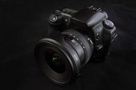 One black camera with wide angle lens isolated on black background, shot from slight;y elevated  viewpoint Stock Photo
