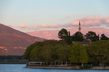 Aslan Pasha mosque built on the lake-shore in the city of Ioannina, Greece, bathed in afternoon light