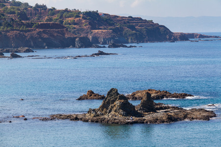 Pomos village seascape in Cyprus with fisherman fishing on an off-shore rock Stock Photo