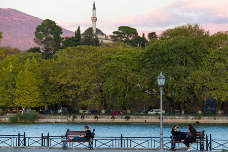 Ioannina, Greece - 5 October, 2017: Girls sitting on benches enjoying themselves by lake Pamvotis in Ioannina with Aslan {asha mosque in the background on a beautiful autumn afternoon