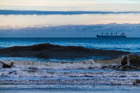 Tall waves and tanker in the distance off King Edwards Bay in Tynemouth, UK on a cold winter morning