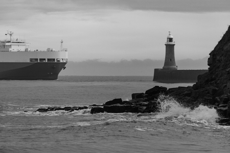 Winter scene in monochrome of waves splashing on rocks, lighhouse and cruising Ferryboat in Tynemouth, UK