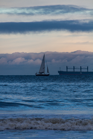 Sailboat and tanker cruising in opposite directions in the rough sea off Tynemouth, UK on a cold winter morning Stok Fotoğraf