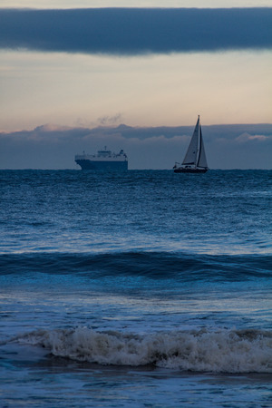 Ferryboat and sailboat cruising in opposite directions in the rough sea off Tynemouth, UK on a cold winter morning