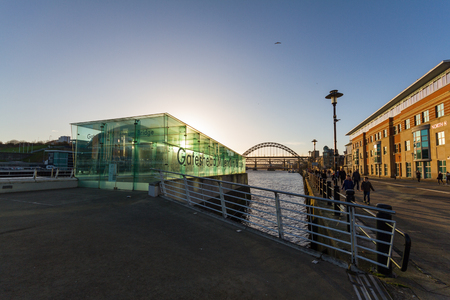 Newcastle, England - December 31, 2017: People walking at Newcastle Quayside near the Entrance to the Gateshead Millennium Bridge in the afternoon on New Years eve