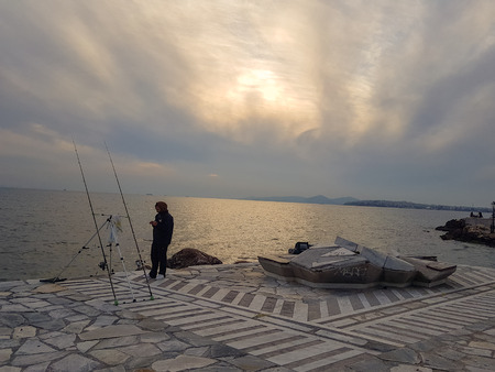 Athens, Greece - February 18, 2018: Man standing near unattended fishing rods on the promenade at Palaio Faliro in Athens, Greece 写真素材 - 103204996