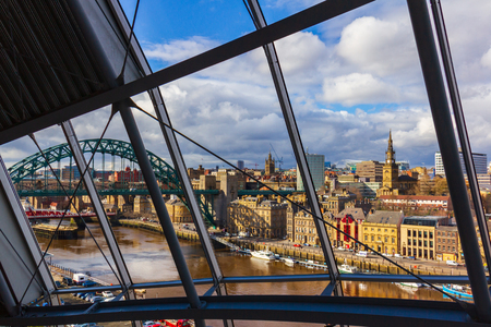 Newcasstle city Skyline through Sage Gateshead windows with River Tyne, Tyne Bridge  and other buildings at Newcastle Quayside in view Stok Fotoğraf - 99769962