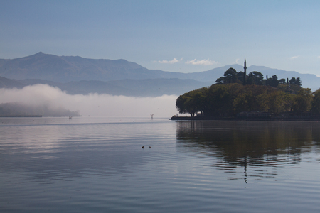 Atmospheric scene of Lake Pamvotis on a misty morning in Ioannina, Greece, with Aslan Pasha mosque in the background- closer view