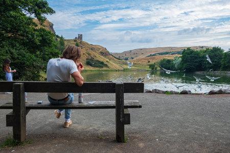 Edynburg, Wielka Brytania - 27 lipca 2018: młody człowiek siedzi i pali na ławce nad jeziorem St Margaret z ruinami kaplicy św. Antoniego w tle.