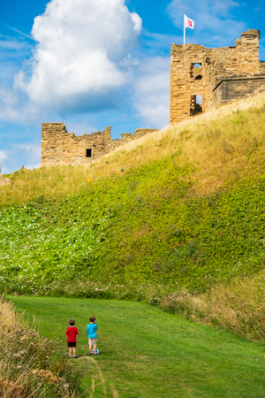 Tynemouth, England - August 2, 2018: Two boys with a football gaze towards Tynemouth Priory and Castle.