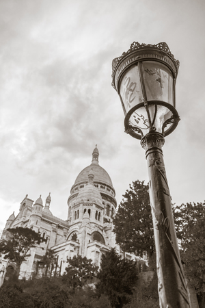 Paris, France - August 7, 2018: Dome of Sacre Coeur Basilica and a classical lampost on Montmartre in Paris, France in sepia tone. Editorial