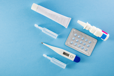Blister pack of blue pills, ampoules, nasal spary, white ointment tube and digital thermometer on blue background- healthcare and medical concept