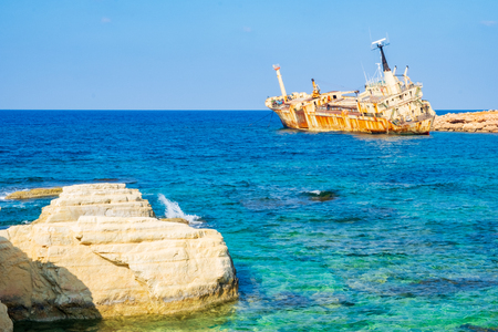 Abandoned rusty ship wreck EDRO III in Pegeia, Paphos, Cyprus. It is stranded on Peyia rocks at kantarkastoi sea caves, Coral Bay, Pafos, standing at an angle near the shore. Stock Photo