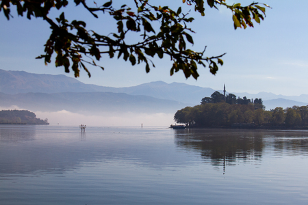 Atmospheric scene of Lake Pamvotis on a misty morning in Ioannina, Greece, with Aslan Pasha mosque in the background