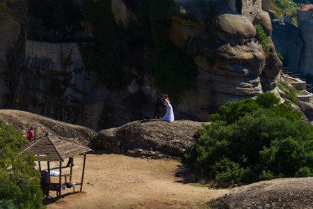 Meteora, Greece - 9 October, 2017: Groom kissing bride on a rock at Meteora Monastery complex in Greece
