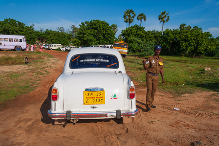 Mahabalipuram, India - September 3, 2007: Indian policeman next to a car policing an open air celebration event in Mahabalipuram.