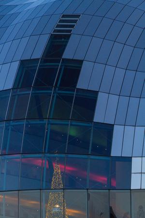 Close-up on exterior glass of Sage Gateshead concert hall on Newcastle Gateshead Quayside with visible illuminated Christmas tree