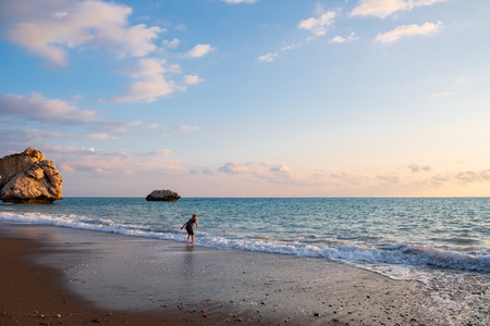 A barefooted boy plays at the beach at the Petra tou Romiou rocks, in Paphos, Cyprus. The beach is considered to be Aphrodite's birthplace in Greek mythology. Stockfoto