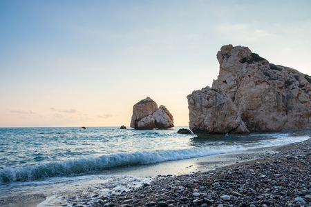 Afternoon view of breaking waves at the pebbly beach around Petra tou Romiou, in Paphos, Cyprus. It is considered to be Aphrodite's birthplace in Greek mythology.