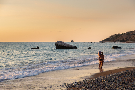 Two girls in swimming suits take a selfie photo at the Petra tou Romiou beach bathed in afternoon light, in Paphos, Cyprus. The beach is considered to be Aphrodite's birthplace in Greek mythology. 免版税图像
