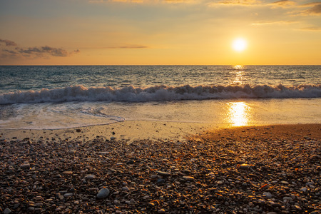 Beautiful sunset view of breaking waves at Petra tou Romiou beach, in Paphos, Cyprus. It is considered to be Aphrodite's birthplace in Greek mythology.