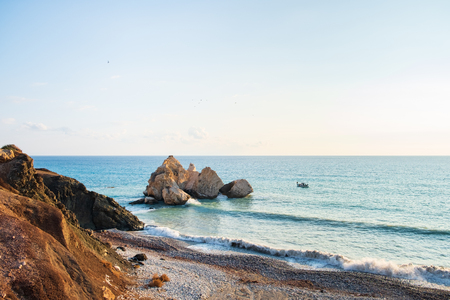 Afternoon view of the seascape around Petra tou Romiou, in Paphos, Cyprus, as a fishing boat passes by. It is considered to be Aphrodite's birthplace in Greek mythology. Stockfoto