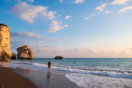 A barefooted boy plays at the beach againt the Petra tou Romiou rocks bathed in afternoon light, in Paphos, Cyprus. The beach is considered to be Aphrodite's birthplace in Greek mythology. Stockfoto
