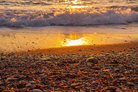 Beautiful beach pebble sunset view at Petra tou Romiou beach, in Paphos, Cyprus. It is considered to be Aphrodite's birthplace in Greek mythology. Stockfoto