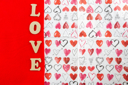 Word LOVE using wooden letters on red and hearts Valentines Day design