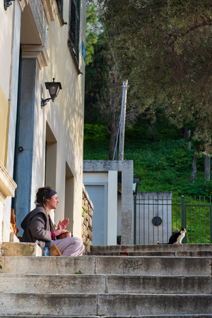 Athens, Greece - March 9, 2019: A hipster girl plays the drum seated on the steps of a house in Plaka Athens near a cat nearby