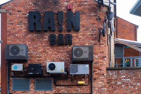 Manchester, United Kingdom - April 25, 2019: Building facade with geometrical patterns of 3D letters and air-conditioning units of Rain Bar overlooking the Bridgewater Canal in the city of Manchester, England.