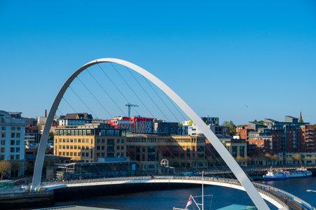 Newcastle, United Kingdom - April 29, 2019: Gateshead Millennium Bridge against the Newcastle cityscape. The bridge spans the River Tyne in north east England.