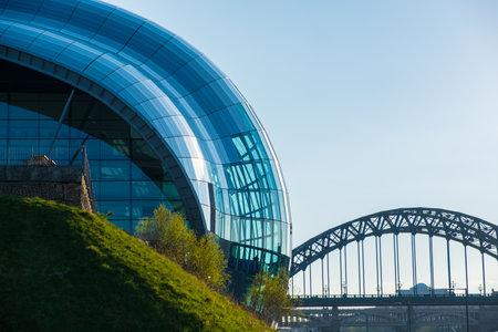 Newcastle, United Kingdom - April 29, 2019: View of the Sage Gateshead and Tyne Bridge against Newcastle cityscape.