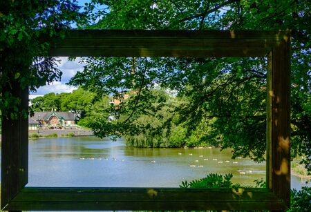 View through large hollow picture frame of trees and birds in pond at Leases Park in Newcastle, England