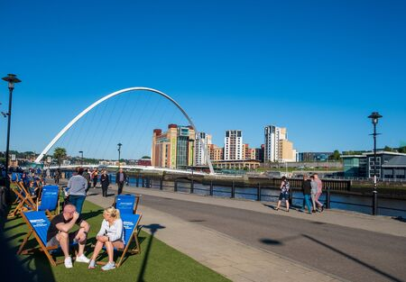 Newcastle, United Kingdom -June 27, 2019: Scene set against the Gateshead Millennium Bridge and the Baltic Centre for Contemporary Art of people enjoying themselves at the Newcastle Quayside on a beautiful summer afternoon. Editorial