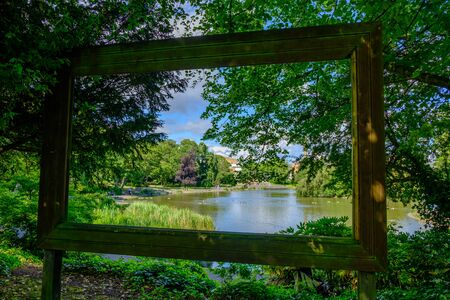 Newcastle, United Kingdom -July 1, 2019: View through large hollow picture frame of pond, trees, ducks and people at Leases Park in Newcastle, England