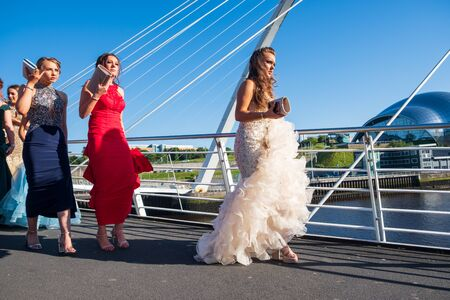 Newcastle, United Kingdom -June 27, 2019: A Bridal and her girlfriends parade in formal dresses and purses on the Millennium Bridge at Newcastle Quayside on a beautiful summer afternoon.